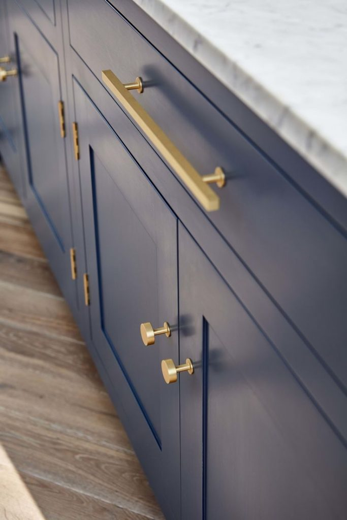 Dark blue shaker style kitchen cabinets with polished brass door handles