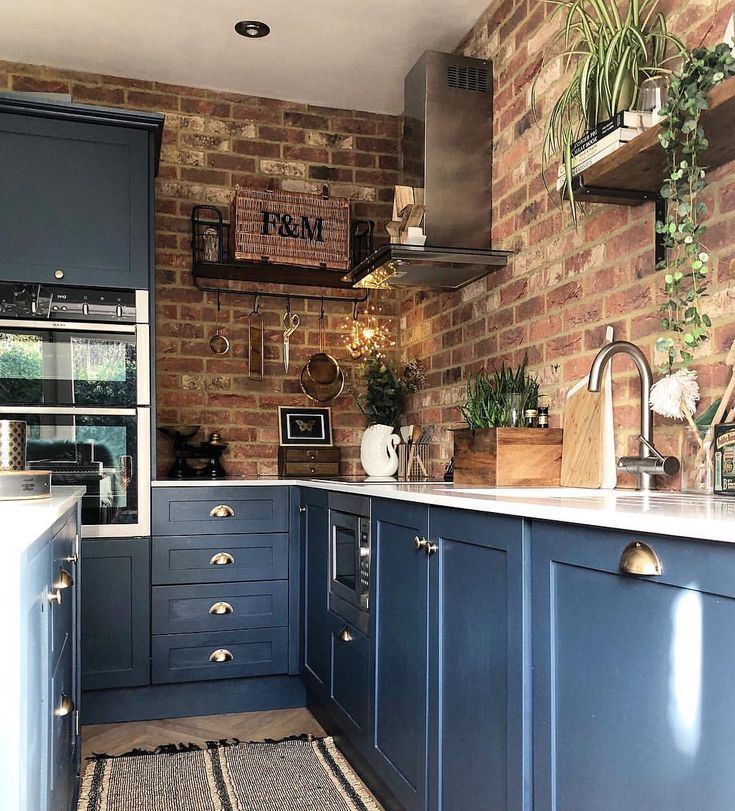 Open brickwork in the kitchen harmonises perfectly with the dark blue ...