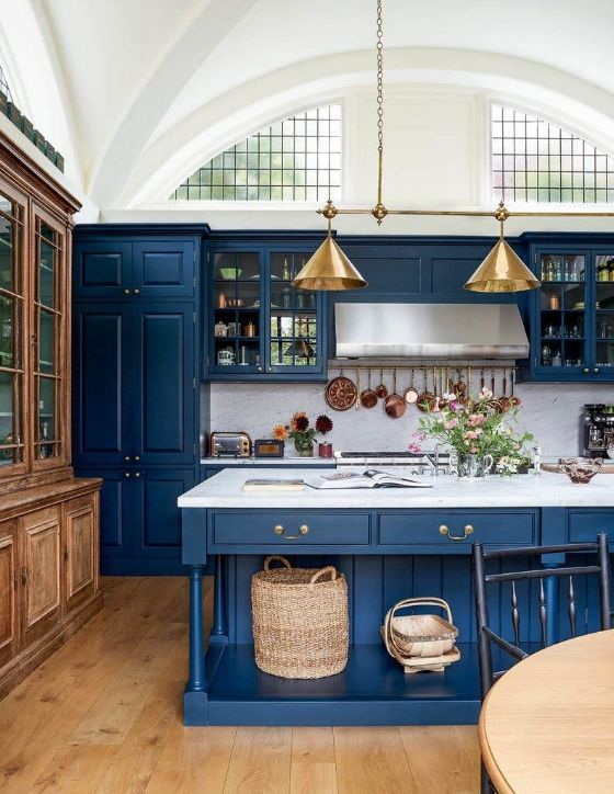A large kitchen window design idea utilizing a large arched window above the cab...
