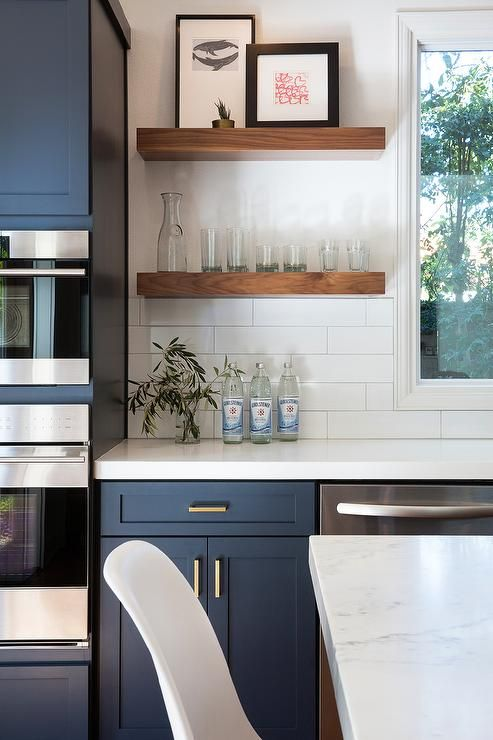 Fantastic kitchen features navy blue shaker cabinets adorned aged brass pulls pa...