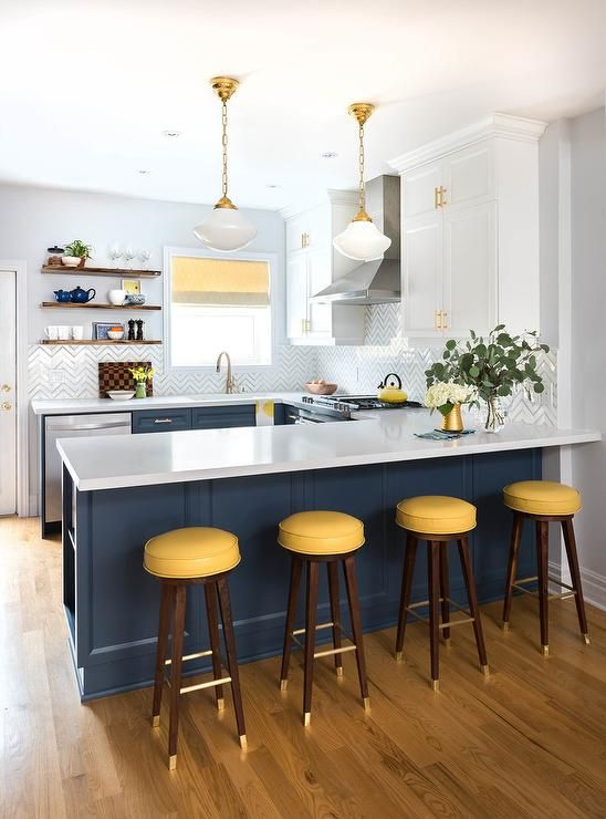 Four yellow backless barstools sit at a blue kitchen peninsula fitted with shelv...