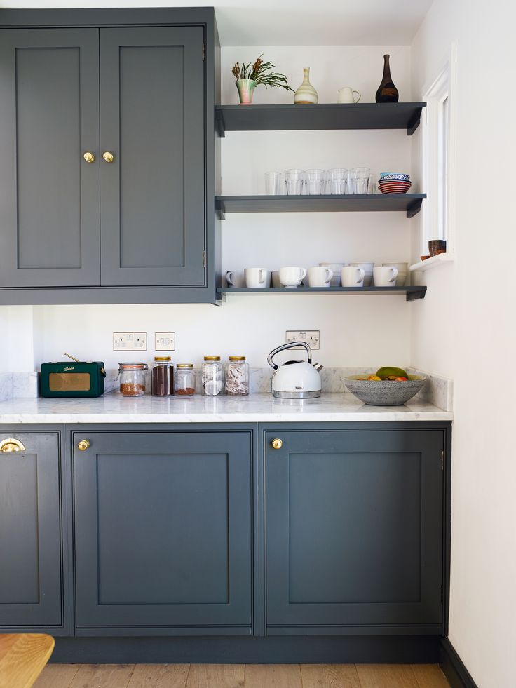 blue kitchen cupboards with marble style worktops and infill shelves