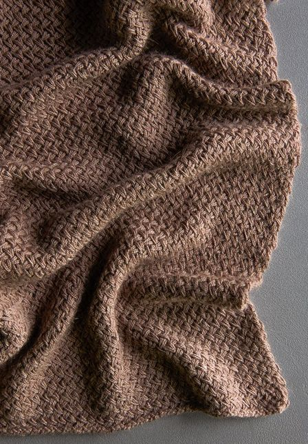 The Plaited Throw is an intermediate knit pattern that looks like dozens of wove...