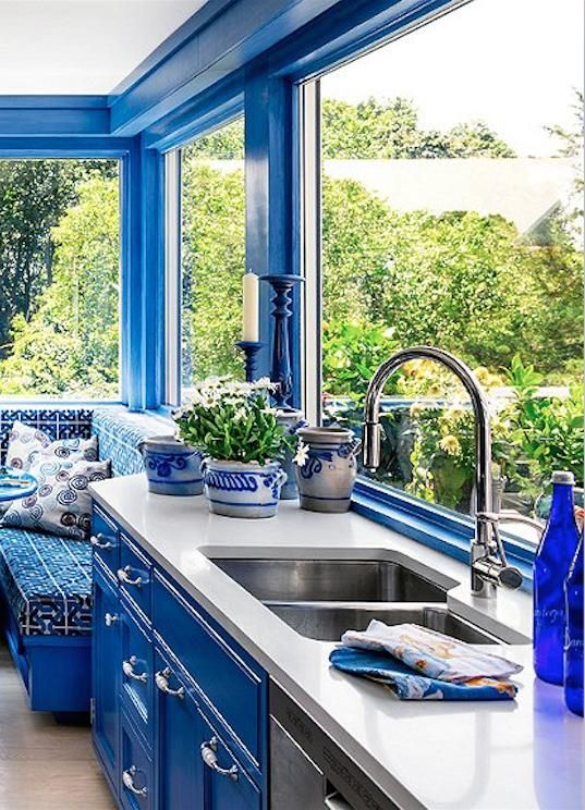Cobalt blue cabinets, window trim and Greek key upholstery fabric on the built-i...