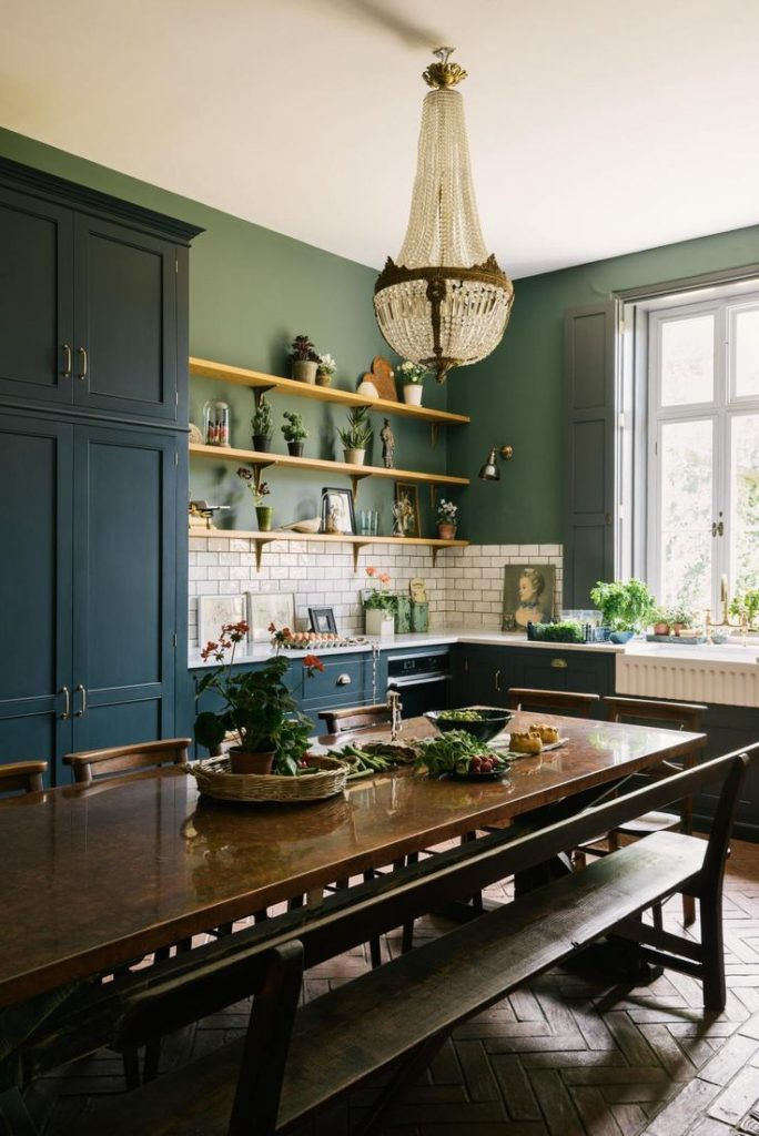 Classic blue kitchen in a Victorian rectory with terracotta floor and green wall...